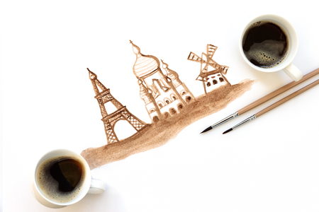 Two cups of espresso with painting brushes and hand drawing attractions of Paris, France. Coffee art or creative concept. Top view