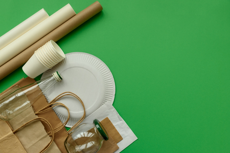 Paper and glass packages on green background. Copy space. Top view. Eco and save earth concept.