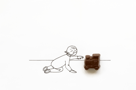 Hand drawing cute cartoon baby playing with chocolate train toy. Minimal, creative or food art concept. Copy space
