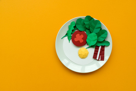 Continental breakfast made from paper: fried egg, tomato, bacon, spinach and arugula on yellow background. Minimal, creative, healthy or food art concept. Copy space. Top view