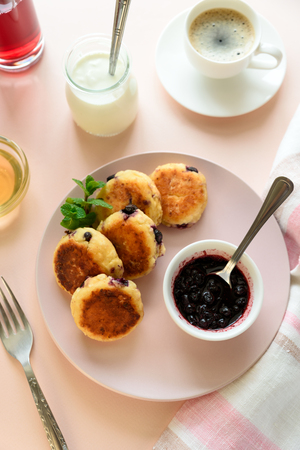 Cottage cheese pancakes with blueberry, honey, jam and coffee. Ukrainian syrniki, cottage cheese fritters or pancakes on pink wooden background. Healthy eating concept. Selective focus