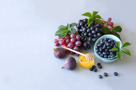 Honey and fresh organic seasonal fruit: grapes, figs and blueberry. Autumn harvest on gray wooden background. Copy space