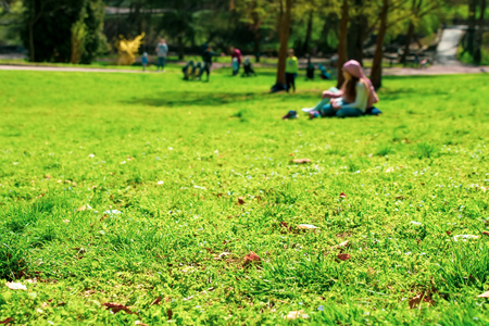 Vibrant background of people in park. Spring and summer season. Selective focus