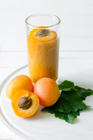 Apricot and banana smoothie glass on white wooden background. Detox and healthy eating concept