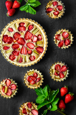 Homemade tarts with strawberry and rhubarb on black wooden background. Top view. Rustic style