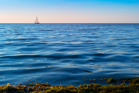Sailboat in the sea in the evening sunlight over sky background. Luxury summer adventure or active vacation concept. Copy space. Stockfoto