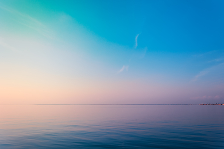 Horizontal sea line in the evening sunlight over sky background. Blue hour sunset. Summer adventure or vacation concept. Copy space.