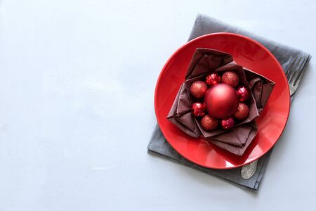 Christmas table setting with red plate, brown napkin in lotos shape and balls on gray wooden background. Holiday decorations concept. Flat lay. Top view. Copy space 免版税图像