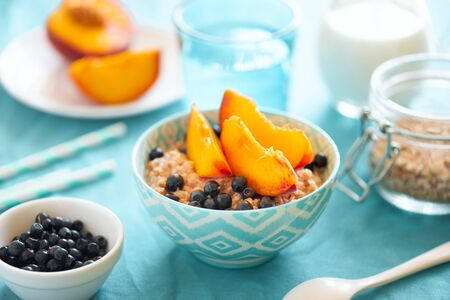 Porridge bowl oatmeal with peach and blueberries on turquoise background. Soft focus. Healthy eating concept.