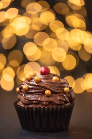 Chocolate cupcake with golden candies on dark wooden background against blurred lights. Selective focus. Unhealthy food.