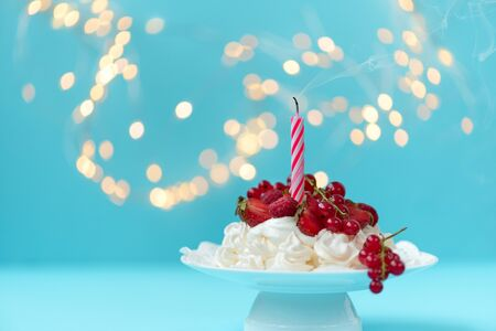 Pavlova birthday fruit cake with blown out candle on pastel blue background against blurred lights. Selective focus. Healthy food or birthday celebration concept. Copy space