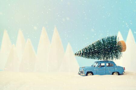 Retro-Autospielzeug mit Weihnachtsbaum in verschneiter Landschaft. Weihnachts- oder Neujahrsfeierkonzept. Platz kopieren. Selektiver Fokus