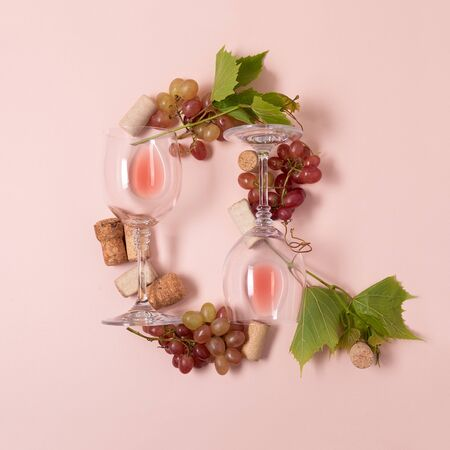Alphabet. Letter Q made of wineglasses with rose and white wine, grapes, leaves and corks lying on pink background. Wine degustation concept. Flat lay. Top view Stock Photo