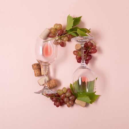 Alphabet. Letter O made of wineglasses with rose and white wine, grapes, leaves and corks lying on pink background. Wine degustation concept. Flat lay. Top view