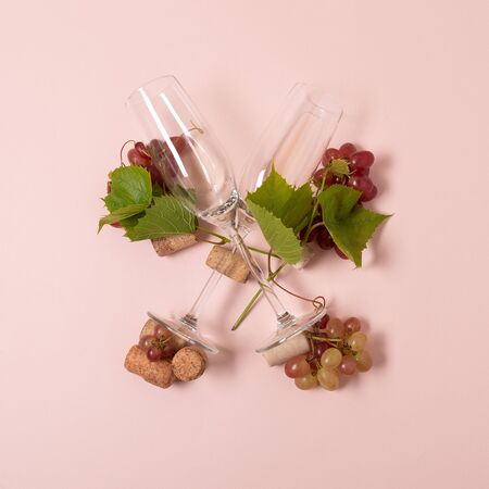 Alphabet. Letter X made of wineglasses with rose and white wine, grapes, leaves and corks lying on pink background. Wine degustation concept. Flat lay. Top view 写真素材