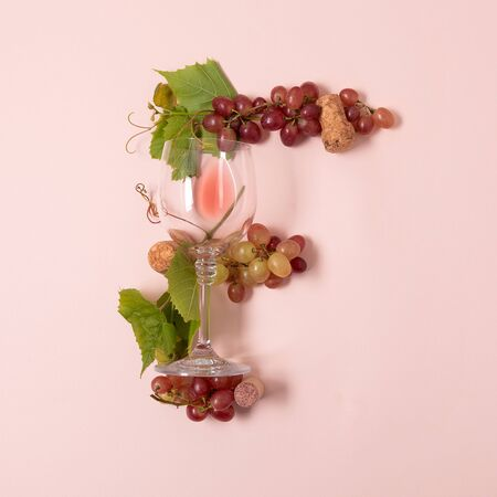 Alphabet. Letter F made of wineglasses with rose and white wine, grapes, leaves and corks lying on pink background. Wine degustation concept. Flat lay. Top view