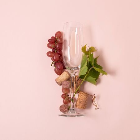 Alphabet. Letter I made of wineglasses with rose and white wine, grapes, leaves and corks lying on pink background. Wine degustation concept. Flat lay. Top view