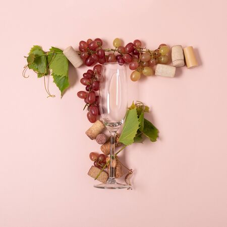 Alphabet. Letter T made of wineglasses with rose and white wine, grapes, leaves and corks lying on pink background. Wine degustation concept. Flat lay. Top view 写真素材