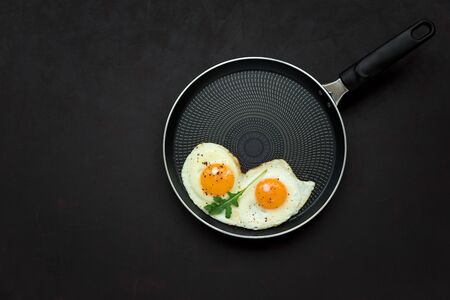 Fried eggs in frying pan with arugula leaves, salt and pepper for breakfast on black wooden background. Top view. Flat lay. Copy space. Healthy food concept Imagens