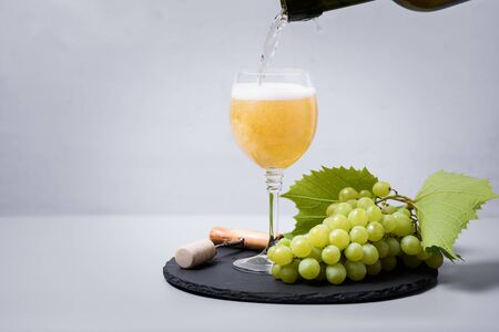 Pouring white wine (champagne) from bottle into wineglass on gray background. Holiday celebration concept