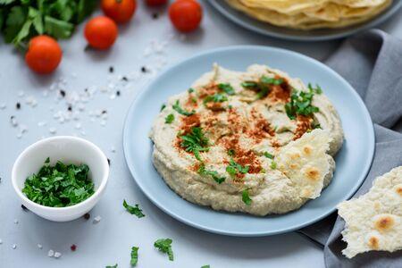 Auberginendip Baba Ganoush (Mutabbal) mit Kräutern und Paprika auf grauem Holzhintergrund. Selektiver Fokus. Traditionelles arabisches Essen Standard-Bild