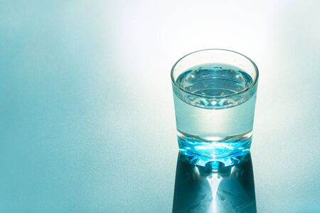 Glass of water with reflecting shadows on blue background. Healthy food concept. Top view. Copy space Archivio Fotografico