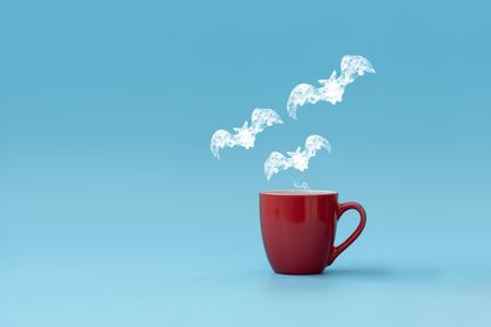 Steam in three bats shape flying from coffee cup against blue background. Morning drink. Halloween celebration concept. Copy