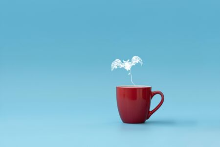 Steam in bat shape flying from coffee cup against blue background. Morning drink. Halloween celebration concept. Copy space. Stock Photo