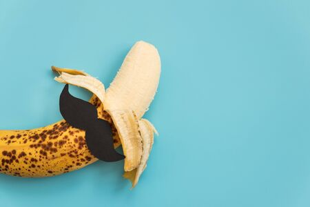Open bad banana with black paper mustache. Sexually transmitted diseases concept. Imagens