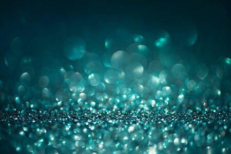 Luci glitter astratte su sfondo turchese. Biglietto di auguri di Natale. Concetto di celebrazione di Natale o Capodanno. Copia spazio. Focalizzazione morbida