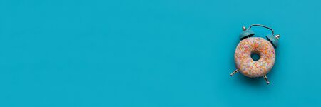 Banner 3:1. Pink alarm clock donut on blue background. Breakfast time or minimal concept. Copy space. Top view