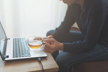 Young adult using laptop and drinking tea. Soft focus. Job at home. Female freelancer. Stok Fotoğraf