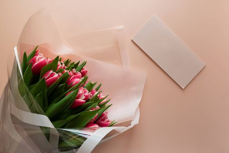 Bouquet of pink tulips with empty card on pink background. Valentines day or Mothers day celebration concept. Top view. Flat lay. Copy space.