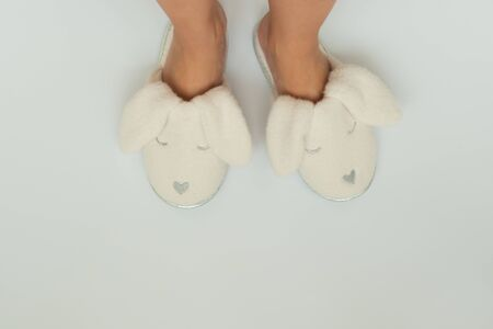 Pink fur slippers in shape of rabbit put on women legs standing on a white background.Top view. Copy space Stok Fotoğraf