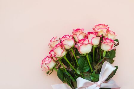 Bouquet of fresh pink roses wrapped pink ribbon on pink background. Top view. Flat lay. Copy space. Valentines day, mothers day or birthday celebration concept