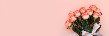 Banner 3:1. Bouquet of fresh pink roses wrapped pink ribbon on pink background. Top view. Flat lay. Copy space. Valentines day, mothers day or birthday celebration concept