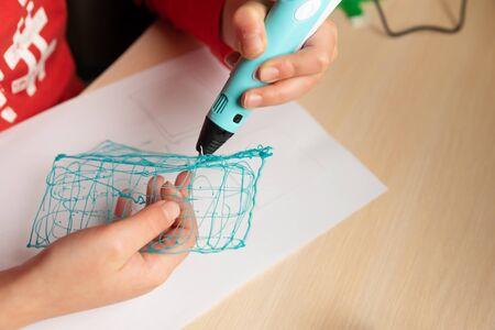 Close-up hands of boy creating volume plastic figure with 3D pen. Selective focus. Education concept Stok Fotoğraf