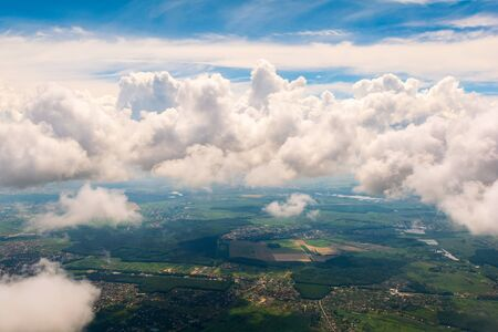 Fluffy clouds over city. Aerial view from airplane window