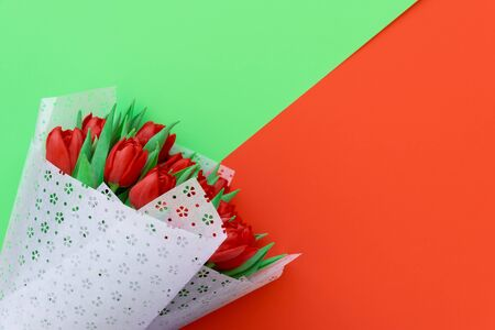 Bouquet of red tulips wrappen in white paper on red and green background. Top view. Flat lay. Copy space. Valentines day, mothers day or birthday celebration concept