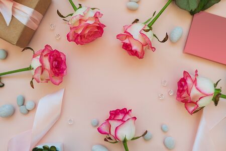 Frame from fresh pink roses, ribbon, gift box, greeting card, beads and pebbles on pink background. Top view. Flat lay. Copy space. Valentines day, mothers day or birthday celebration concept