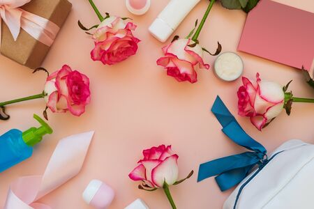 Frame from fresh pink roses, set of cosmetic tubes, jar and bottle, gift box and greeting card on pink background. Top view. Flat lay. Copy space. Valentines day, mothers day, birthday celebration or clean beauty concept