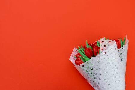 Bouquet of red tulips wrappen in white paper on red background. Top view. Flat lay. Copy space. Valentines day, mothers day or birthday celebration concept