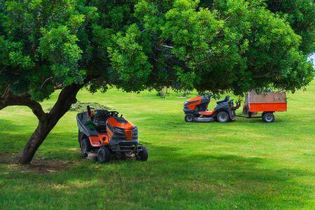 Lawn mower machines on green field. Summer garden ritual
