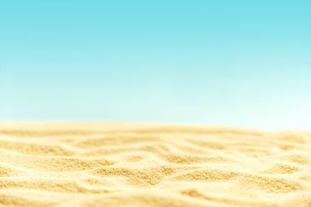 Tropical sandy beach with blurry blue ocean and sky. Summer background. Soft focus