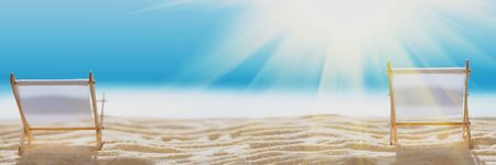 Banner 3:1. Deck chairs on sandy beach with blurry blue ocean and sun beams on sky. Social distancing or COVID-19 protection at summer holidays. Summer background. Soft focus 免版税图像