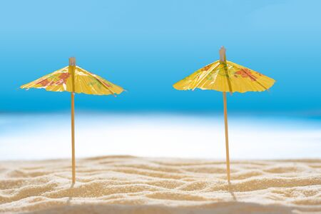 Sun umbrellas on sandy beach with blurry blue ocean and sky. Social distancing or COVID-19 protection at summer holidays. Summer background. Soft focus 免版税图像