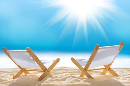 Deck chairs on sandy beach with blurry blue ocean and sun beams on sky. Social distancing or COVID-19 protection at summer holidays. Summer background. Soft focus 免版税图像