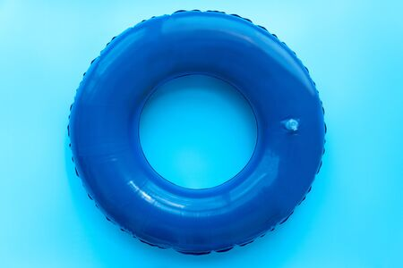 Front view of blue rubber ring for swimming pool on blue background. Top view