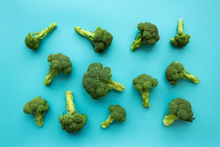 Healthy green organic raw broccoli florets on blue background. Flat lay. Top view