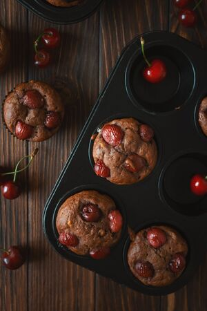 Healthy vegan banana cherry muffins with fresh berries on brown wooden background. Top view. Summer food